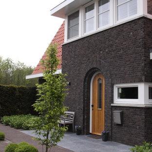 Contemporary brick exterior home idea in Amsterdam