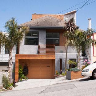 Imagen de fachada de casa pareada multicolor, ecléctica, de tres plantas, con revestimientos combinados, tejado a cuatro aguas y tejado de teja de madera