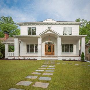 Foto della facciata di una casa unifamiliare bianca classica a due piani con tetto a padiglione e copertura mista