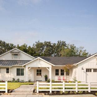 Cette image montre une façade de maison blanche rustique de taille moyenne et de plain-pied avec un toit mixte et un toit à deux pans.