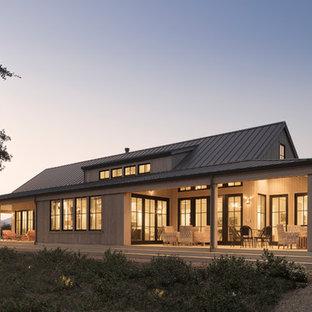 На фото: одноэтажный, деревянный, серый частный загородный дом в стиле кантри с двускатной крышей и металлической крышей с