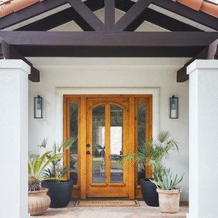 Diseño de fachada de casa blanca, mediterránea, grande, a niveles, con revestimiento de estuco