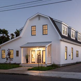 На фото: двухэтажный, деревянный, белый дом среднего размера в стиле кантри с мансардной крышей с