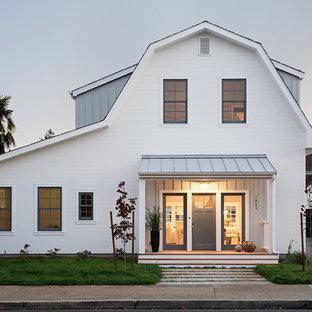 Свежая идея для дизайна: двухэтажный, деревянный, белый дом среднего размера в стиле кантри с мансардной крышей - отличное фото интерьера