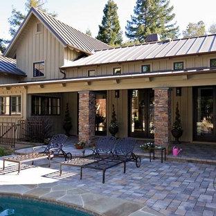Diseño de fachada de casa beige, bohemia, extra grande, de una planta, con revestimiento de madera, tejado a dos aguas y tejado de metal