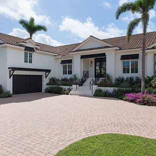 Transitional white two-story stucco gable roof photo in Miami with a tile roof