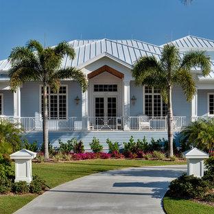 マイアミのトロピカルスタイルのおしゃれな寄棟屋根の家 (青い外壁) の写真