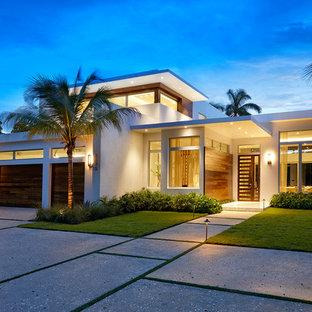 Cette photo montre une grand façade de maison blanche moderne à un étage avec un toit plat, un revêtement en stuc et un toit végétal.