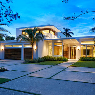 Large modern white two-story stucco exterior home idea in Miami with a green roof