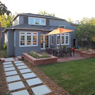 Ejemplo de fachada gris, de estilo americano, a niveles, con revestimiento de estuco