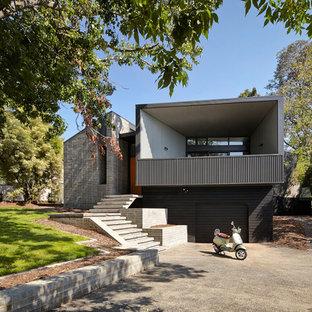 Idee per la facciata di una casa grigia contemporanea a due piani con rivestimenti misti e tetto piano