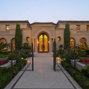 Mediterranean beige two-story adobe house exterior idea in Orange County with a tile roof