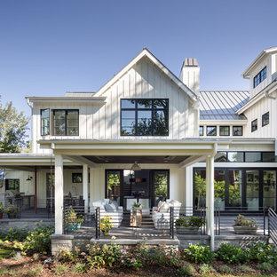 На фото: двухэтажный, деревянный, белый частный загородный дом в стиле кантри с двускатной крышей и металлической крышей с