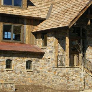 Foto de fachada beige, rústica, grande, de dos plantas, con revestimientos combinados y tejado a doble faldón