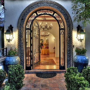 Inspiration for a large southwestern beige two-story adobe exterior home remodel in Phoenix with a clipped gable roof