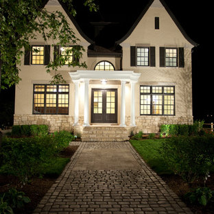 Example of a large classic beige two-story brick exterior home design in Chicago