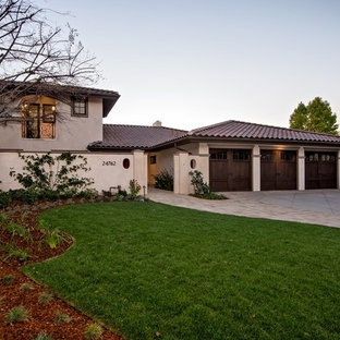Example of a huge tuscan beige two-story stucco exterior home design in Orange County with a clipped gable roof