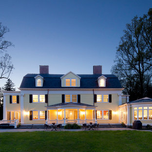 Mid-sized elegant yellow three-story wood exterior home photo in New York with a gambrel roof and a shingle roof