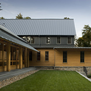 Example of a transitional brown two-story wood exterior home design in Charlotte with a metal roof
