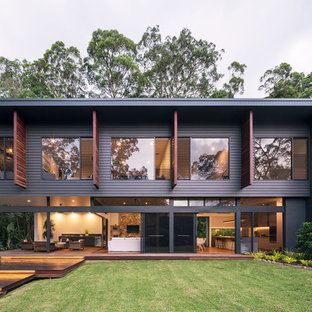 Mid-sized contemporary two-storey black house exterior in Sunshine Coast with concrete fiberboard siding, a flat roof and a metal roof.
