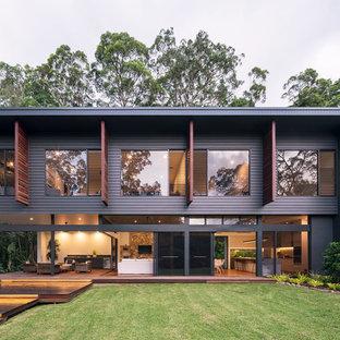Modelo de fachada de casa negra, contemporánea, de tamaño medio, de dos plantas, con revestimiento de aglomerado de cemento, tejado plano y tejado de metal