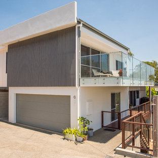 Photo of a large contemporary concrete white house exterior in Sunshine Coast with a flat roof and three or more storeys.