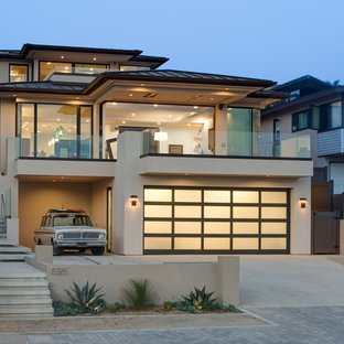 Trendy beige three-story exterior home photo in San Diego with a hip roof and a metal roof