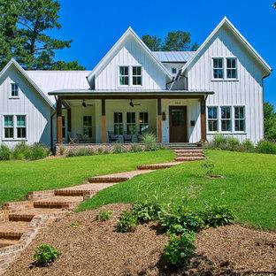 Ispirazione per la facciata di una casa unifamiliare bianca country a due piani di medie dimensioni con rivestimento con lastre in cemento, tetto a capanna e copertura in metallo o lamiera