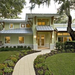 タンパのコンテンポラリースタイルのおしゃれな家の外観 (漆喰サイディング、緑の外壁、半切妻屋根、戸建、金属屋根) の写真