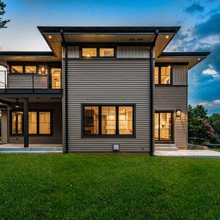 Источник вдохновения для домашнего уюта: двухэтажный, серый частный загородный дом среднего размера в современном стиле с облицовкой из винила, односкатной крышей и крышей из гибкой черепицы