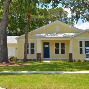 Diseño de fachada de casa amarilla, de estilo americano, de una planta, con revestimiento de aglomerado de cemento, tejado de metal y tejado de un solo tendido