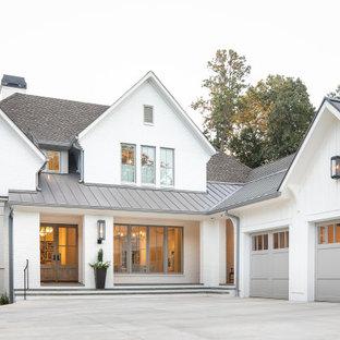 На фото: белый частный загородный дом в стиле кантри с двускатной крышей и крышей из смешанных материалов