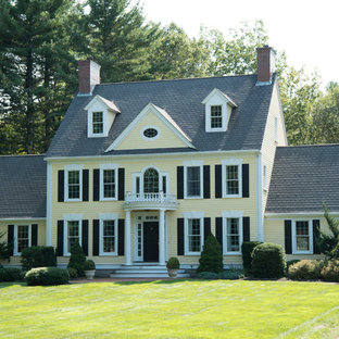 Inspiration for a mid-sized timeless yellow two-story wood gable roof remodel in Boston
