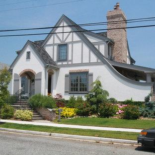 Modelo de fachada blanca, bohemia, grande, de dos plantas, con revestimiento de estuco y tejado a dos aguas