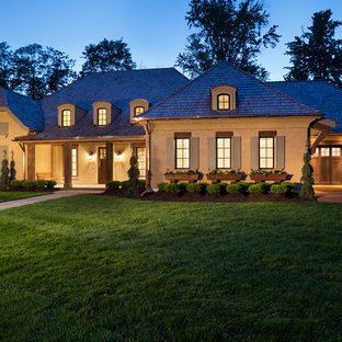 Large transitional beige one-story stucco house exterior idea in Minneapolis with a shingle roof