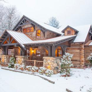 На фото: большой, двухэтажный, деревянный дом из бревен в стиле рустика с двускатной крышей и металлической крышей для охотников