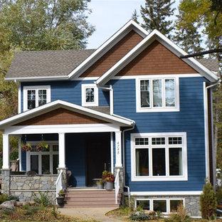 Modelo de fachada de casa azul, de estilo americano, de tamaño medio, de dos plantas, con revestimiento de aglomerado de cemento, tejado a dos aguas y tejado de teja de madera