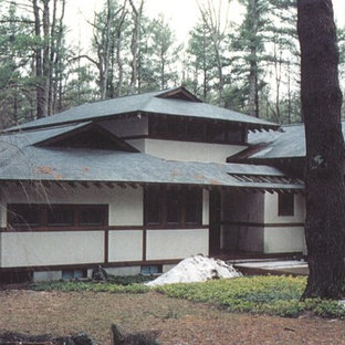 Photo of a large asian two-storey stucco white house exterior in Other with a shingle roof.