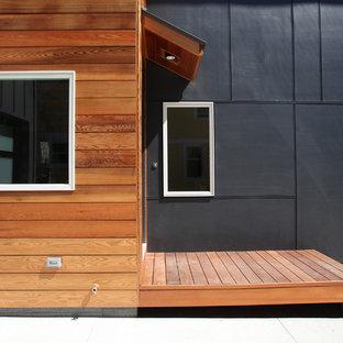 Foto de fachada de casa gris, actual, de tamaño medio, de dos plantas, con revestimientos combinados, tejado a dos aguas y tejado de teja de madera