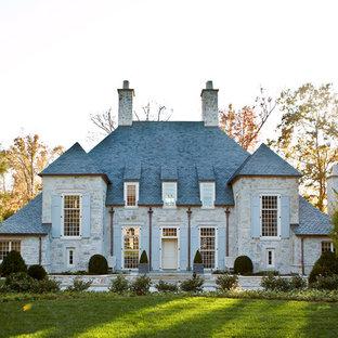 Ispirazione per la facciata di una casa unifamiliare grigia classica a due piani di medie dimensioni con rivestimento in pietra, tetto a padiglione e copertura a scandole