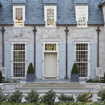 Example of a mid-sized classic gray two-story stone house exterior design in Charlotte with a hip roof and a shingle roof