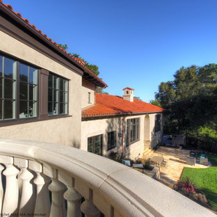 Example of a large tuscan beige split-level stucco gable roof design in San Francisco