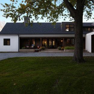 Ejemplo de fachada de casa blanca, de estilo de casa de campo, de tamaño medio, de dos plantas, con revestimiento de madera, tejado a dos aguas y tejado de teja de madera
