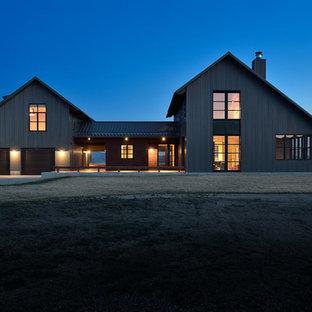Идея дизайна: двухэтажный, серый, большой дом в стиле кантри с облицовкой из металла и двускатной крышей