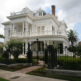 Large victorian house exterior in New Orleans with three floors and wood cladding.