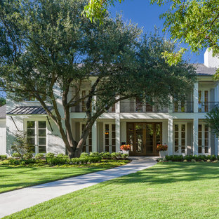 Inspiration for a large timeless white two-story brick house exterior remodel in Dallas with a hip roof and a shingle roof