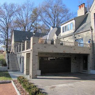 Imagen de fachada de casa gris, de estilo americano, extra grande, a niveles, con revestimiento de ladrillo, tejado a la holandesa y tejado de teja de madera