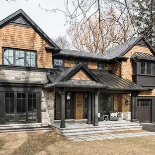 Ispirazione per la facciata di una casa unifamiliare marrone rustica a due piani con rivestimenti misti, tetto a capanna e copertura a scandole