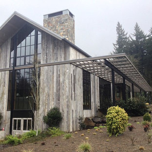 Inspiration for a large farmhouse beige wood exterior home remodel in Portland with a metal roof