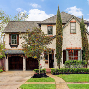 Inspiration for a timeless beige two-story brick house exterior remodel in Houston with a hip roof and a shingle roof